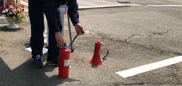 消火器を地面に置き上から体重をかける