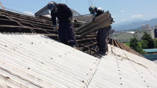 スレート屋根撤去の様子。作業員はマスクをします。撤去した廃材は石綿含有産業廃棄物になります。